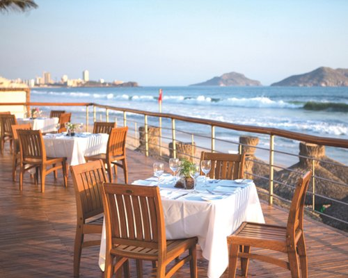Outdoor restaurant with ocean view alongside the beach.