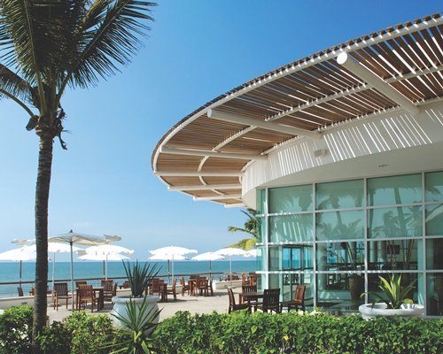 Scenic exterior view of an outdoor restaurant with sunshades alongside the ocean.