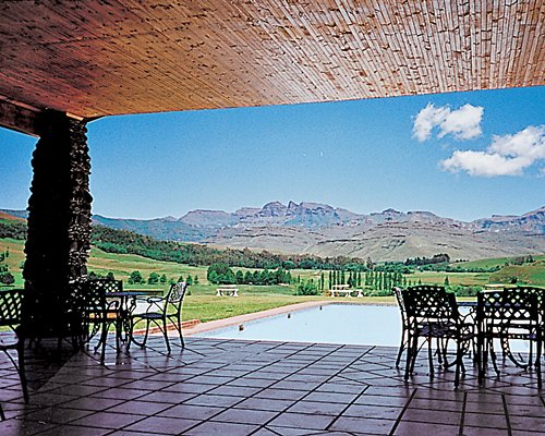 Outdoor swimming pool with an outdoor dining alongside wooded area and mountains.