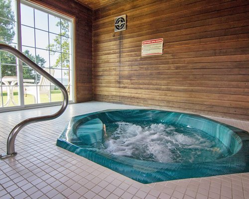 An indoor hot tub with an outside view.