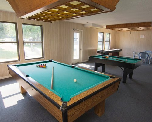 Indoor recreation room with pool tables and outside view.