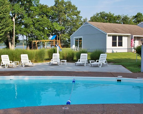 Outdoor swimming pool with chaise lounge chairs alongside a unit and kids playscape.