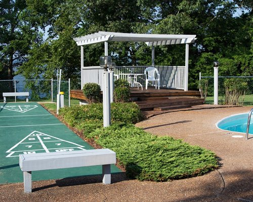 An outdoor shuffleboard alongside patio and swimming pool.