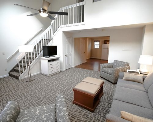 A well furnished living room with a television dining area open plan kitchen and a stairway.
