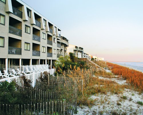Exterior view of multiple unit balconies with a wall alongside the ocean.