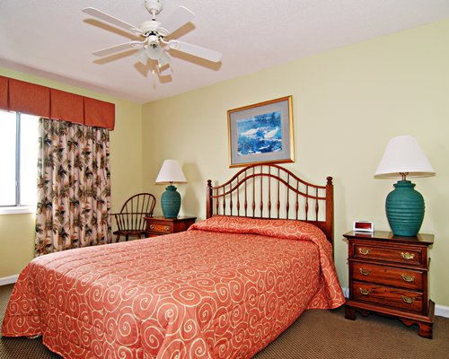 A well furnished bedroom with a queen bed and an outside view.