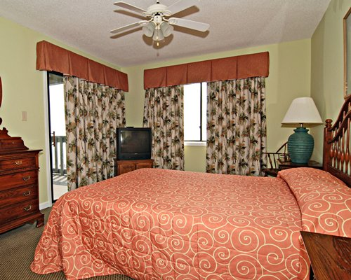 A well furnished bedroom with a queen bed television and outdoor view.