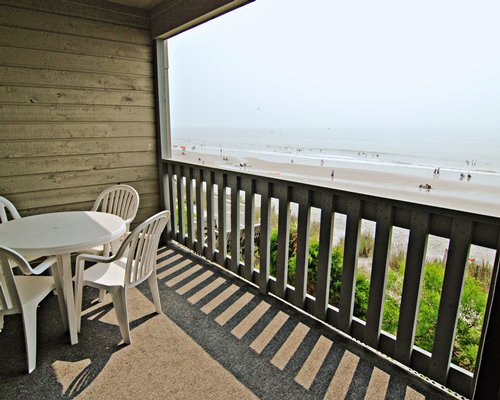 Balcony with patio chairs and ocean view.
