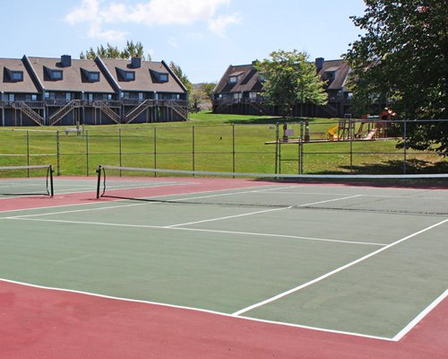 Outdoor recreation area with tennis court alongside kids playscape and multiple units with balconies.