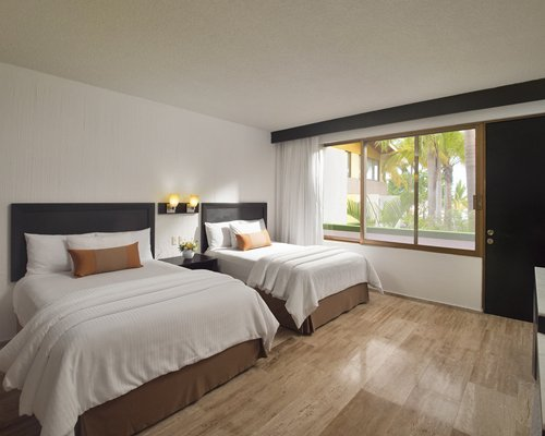 A well furnished bedroom with two twin beds television and outside view.