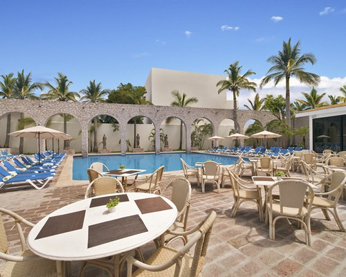 Outdoor swimming pool with chaise lounge chairs and pool side bar alongside multiple unit balconies.
