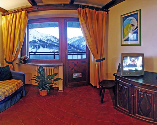 A well furnished living room with television and an outside view.