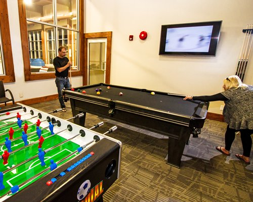 An indoor recreational room with pool and soccer table with television.