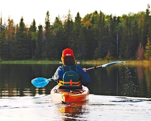 A woman kayaking in the lake surrounded by a wooded area.