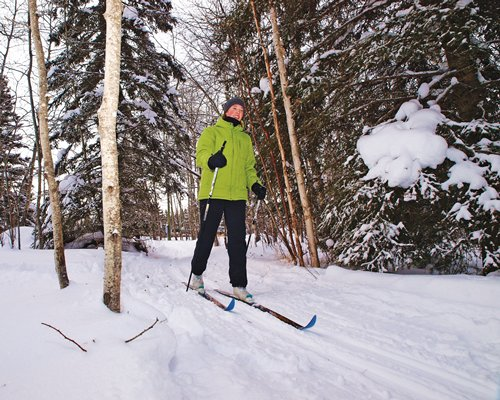 A man skiing in the resort property covered in snow.