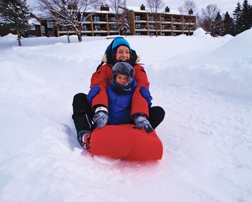 View of two people sledding in the snow.