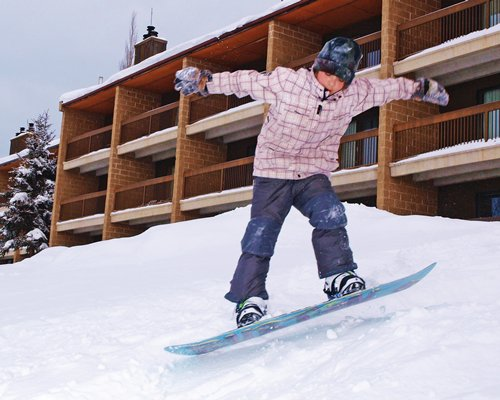 A boy skiing in the snow alongside the resort unit.
