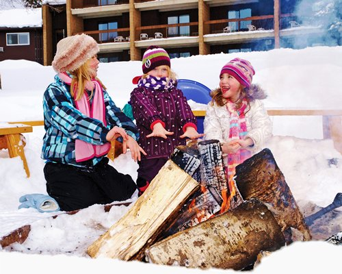 A family in the campfire alongside the resort unit covered in snow.