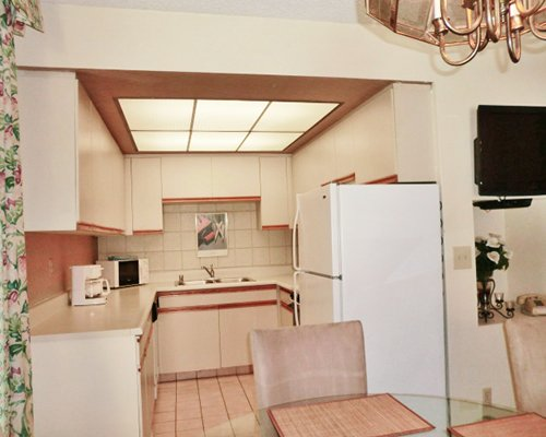 A well equipped kitchen and dining area with television.