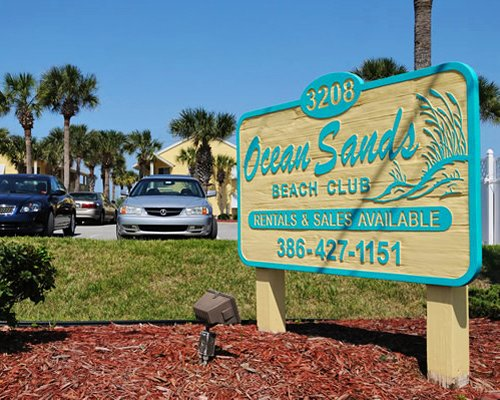 Exterior view and signboard of Ocean Sands At New Smyrna Waves with parking lot and palm trees.