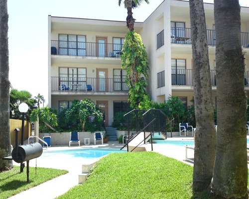 An exterior view of the outdoor swimming pool with chaise lounge chairs alongside resort units.