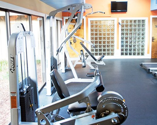 A well equipped fitness center with a television.