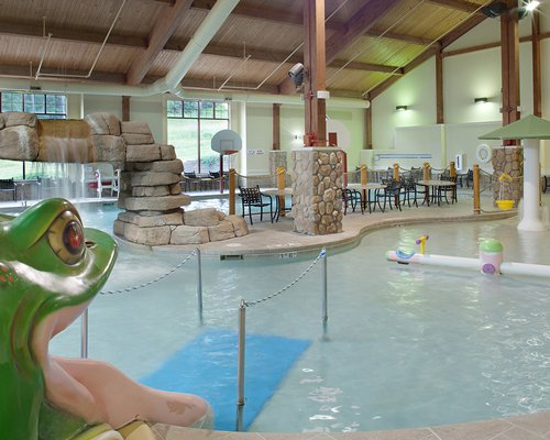 An indoor swimming pool with water fountain alongside patio furniture.