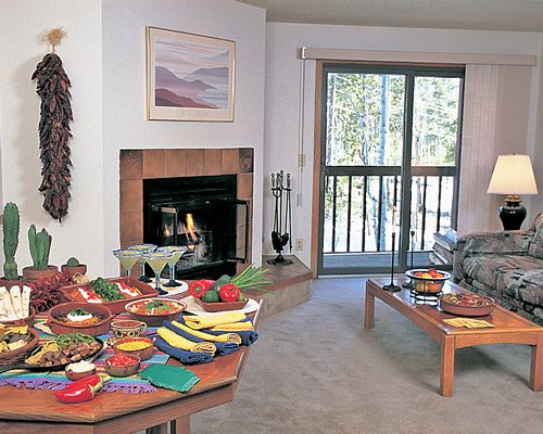 An open plan living and dining area with various foods and a fireplace.