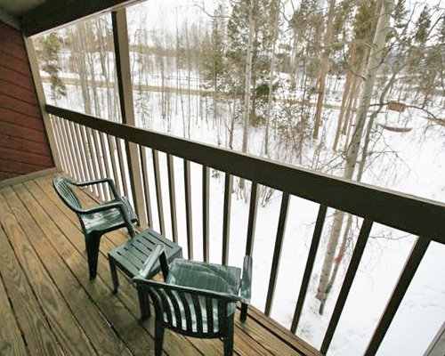View of wooded area from the balcony with patio furniture during winter.