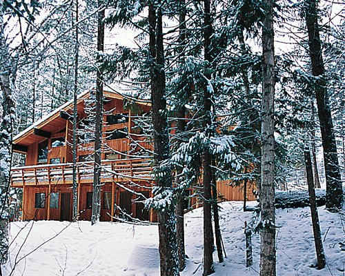 Exterior view of a unit with balcony at Ptarmigan Village surrounded by wooded area during winter.