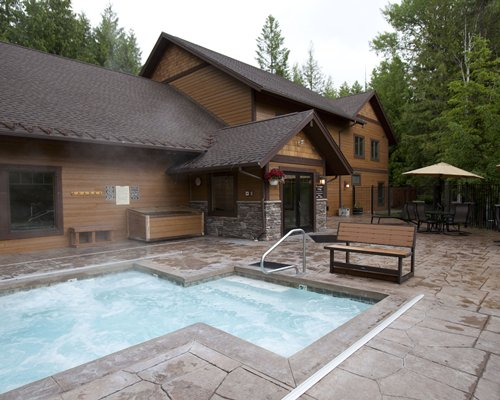 Outdoor swimming pool with outdoor dining alongside a unit at Ptarmigan Village at Whitefish.