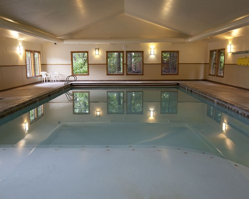 Large indoor swimming pool with patio chairs.