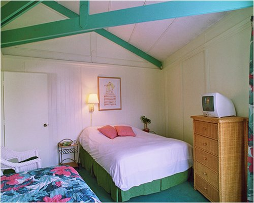 A well furnished bedroom with a queen bed and television.