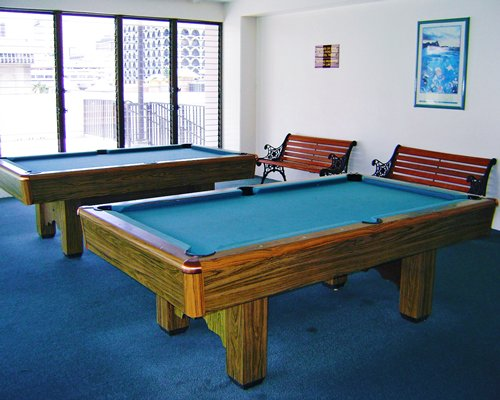 An indoor recreation room with two pool tables.