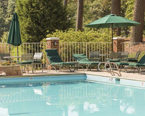 Outdoor swimming pool with chaise lounge chairs sunshades and patio furniture surrounded by wooded area.
