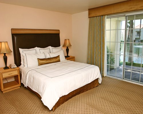 A well furnished bedroom with queen bed and patio.