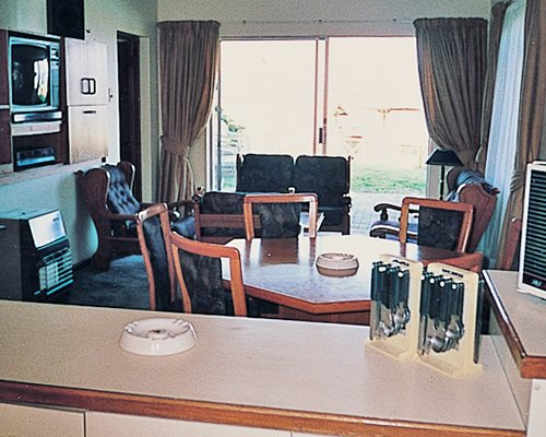 A well furnished bedroom with a television dining area and outdoor view.