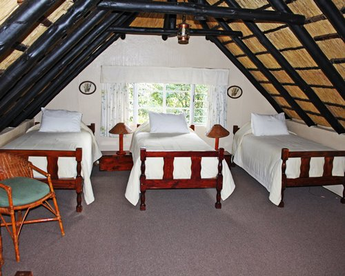 A well furnished bedroom with three twin beds and outside view.