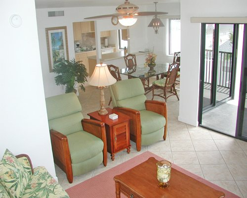A well furnished living room with dining area open plan kitchen and patio.
