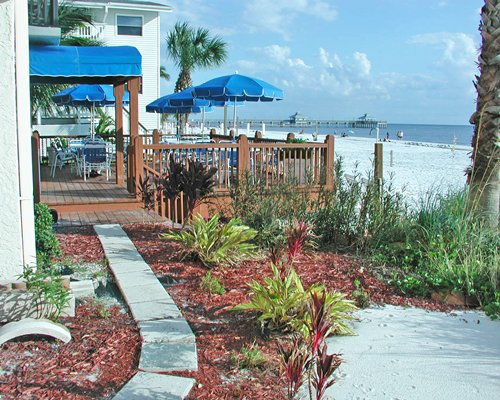Scenic pathway leading to the resort with patio furniture and sunshade.