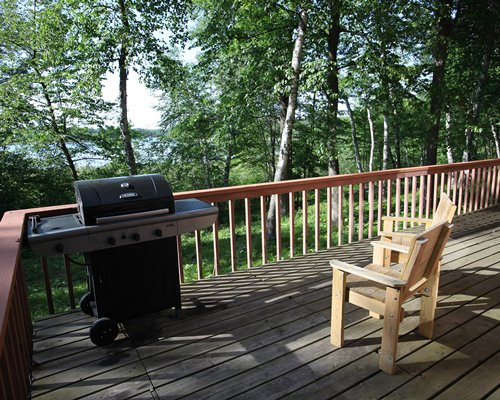 Outdoor picnic area with barbecue grill and view of wooded area.
