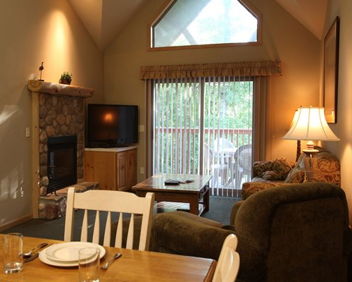 A well furnished living and dining area with television fireplace and an outside view.
