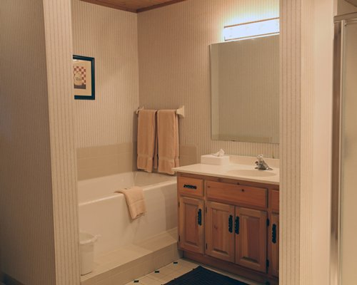 A bathroom with a bathtub shower single sink vanity and mirror.