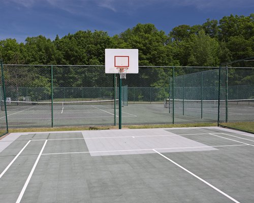 An outdoor basketball court alongside tennis courts surrounded by trees.