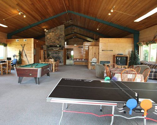 An indoor recreation room with television ping pong and pool table.