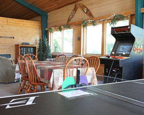 An open plan living and dining area with a television and arcade game.