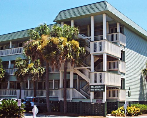 Exterior view of Isle Of Palms Resort with multiple balconies stairways and palm trees.
