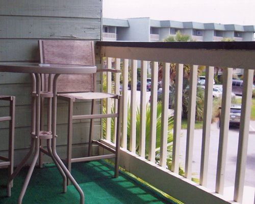 A balcony with patio furniture alongside the resort with a parking lot.