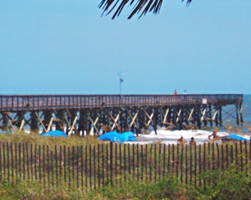 View of people on the beach alongside a wooden pier.