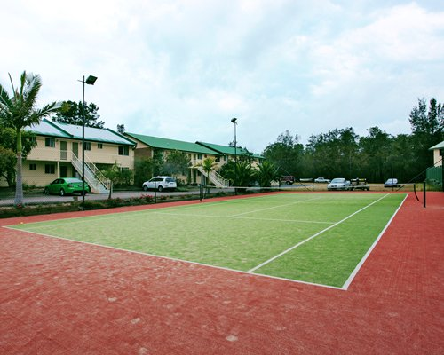 An outdoor tennis court alongside the resort units.